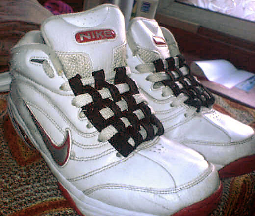 White Nike sneakers with red & grey trim and black & white Checkerboard Lacing (from Hamid A-J)